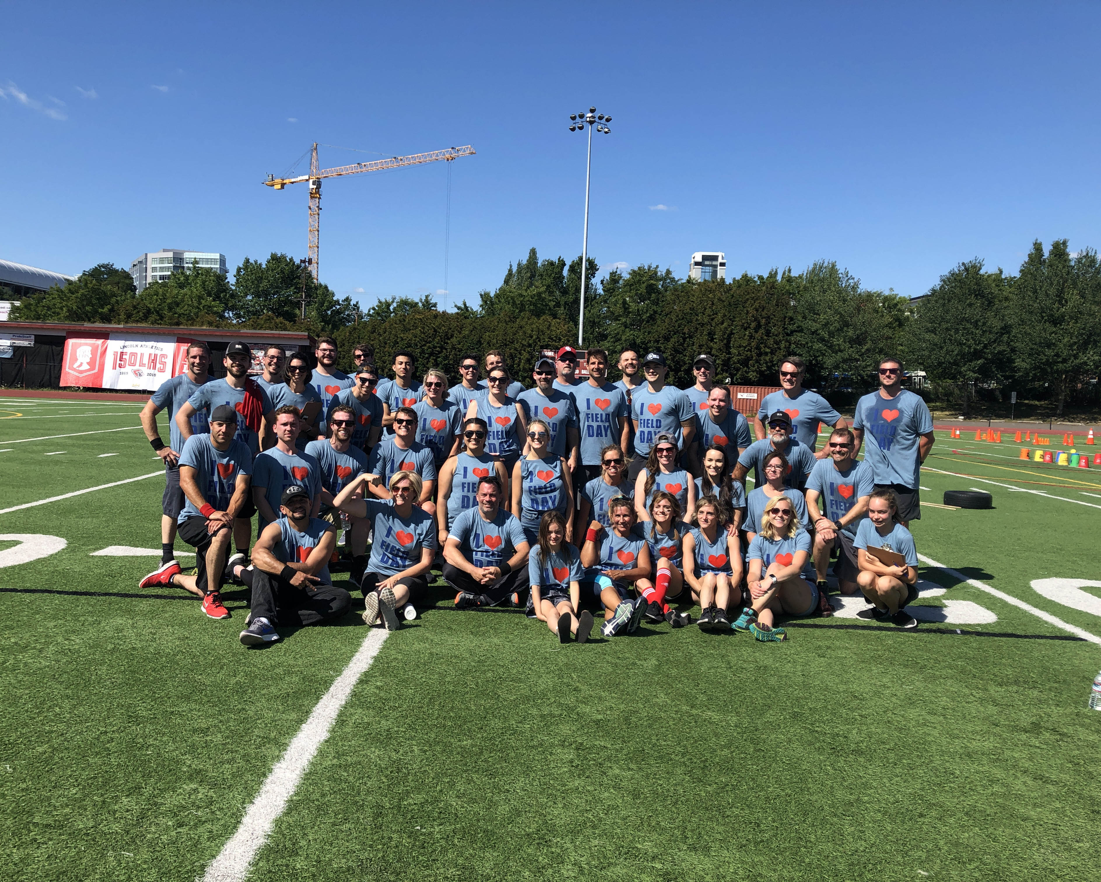 Group shot of R&H employees on football field for field day