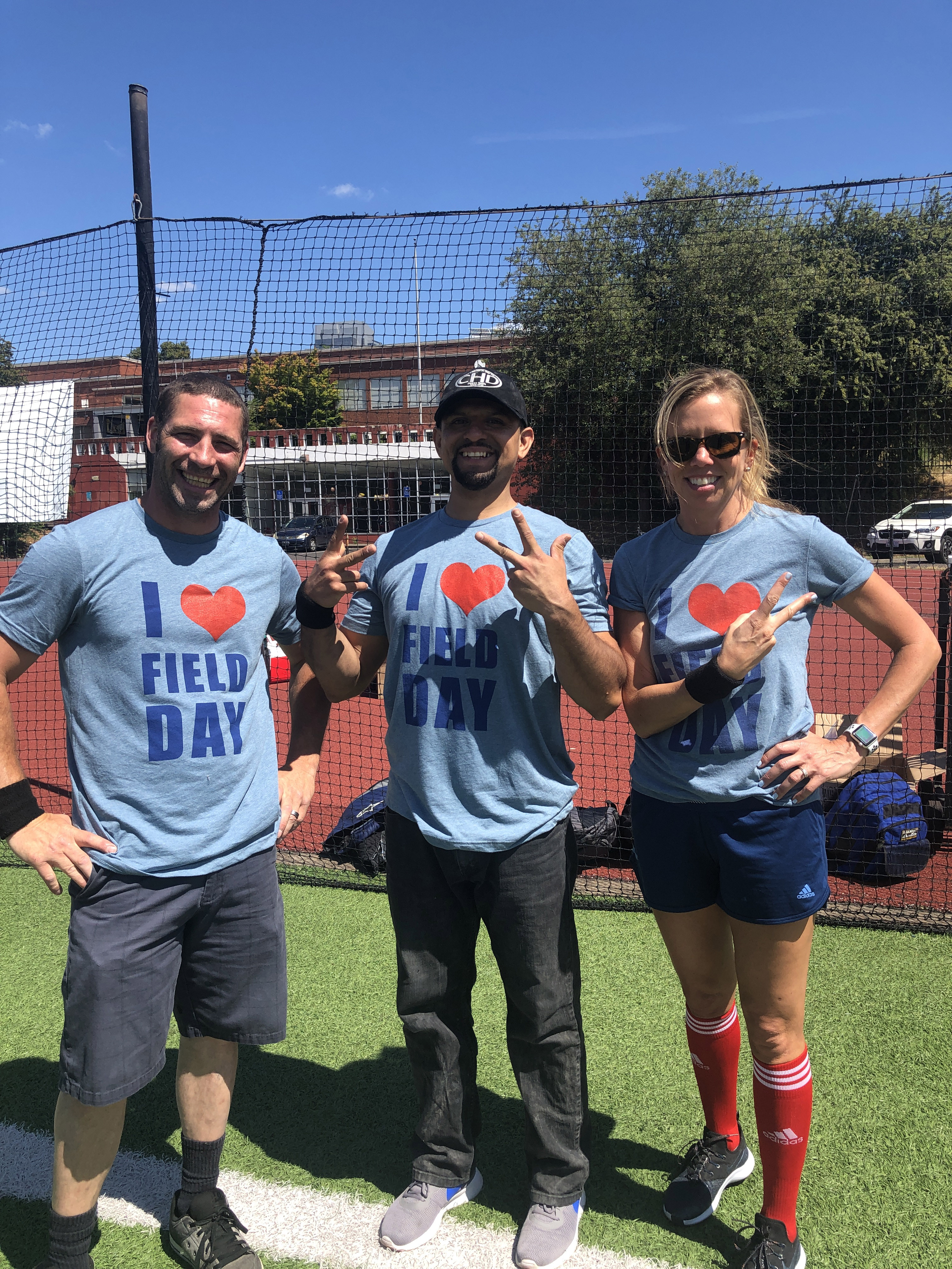 Three R&H employees posing in custom t-shirts for R&H field day on the football field