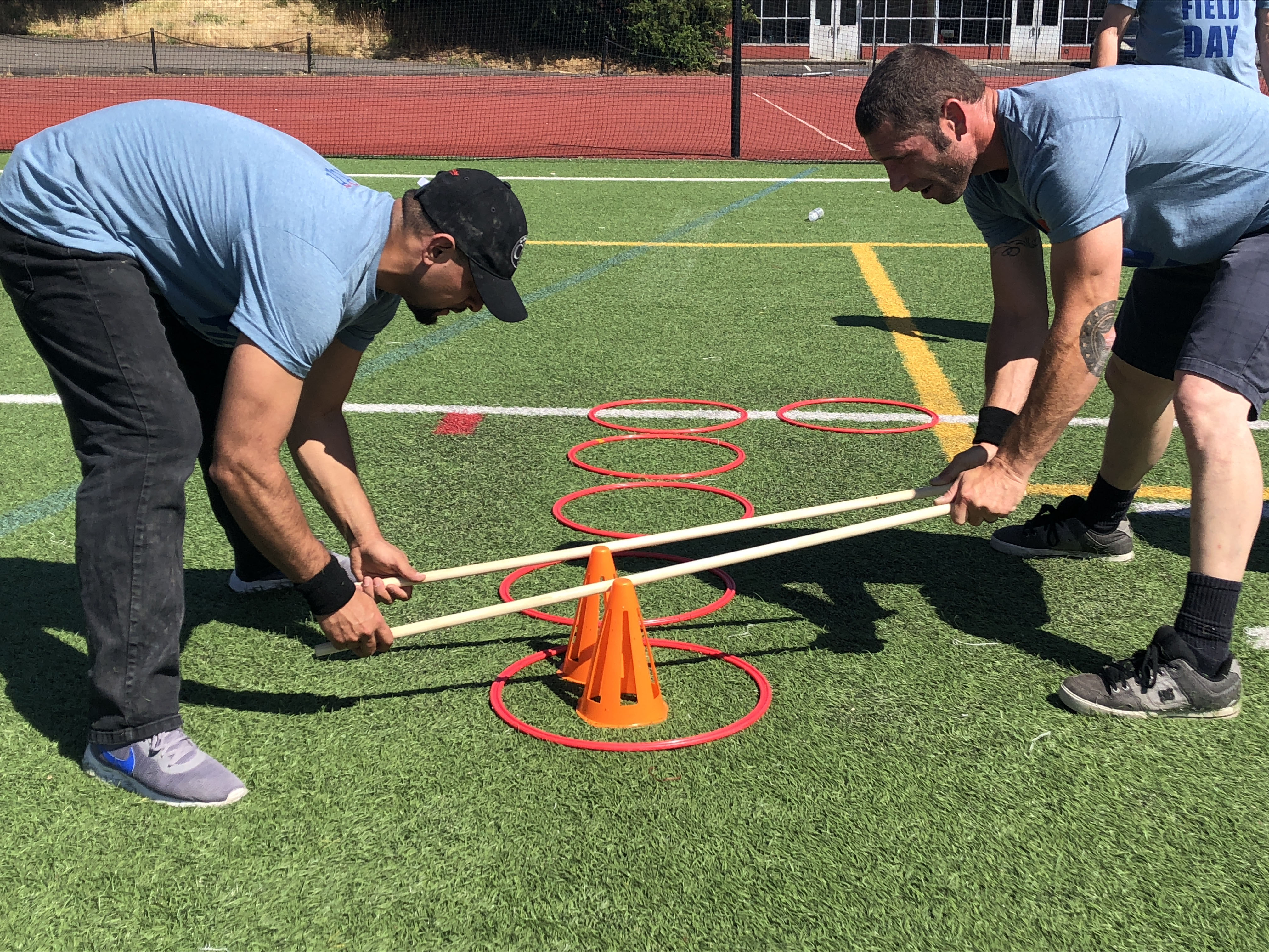 two R&H employees doing field day activities on the football field