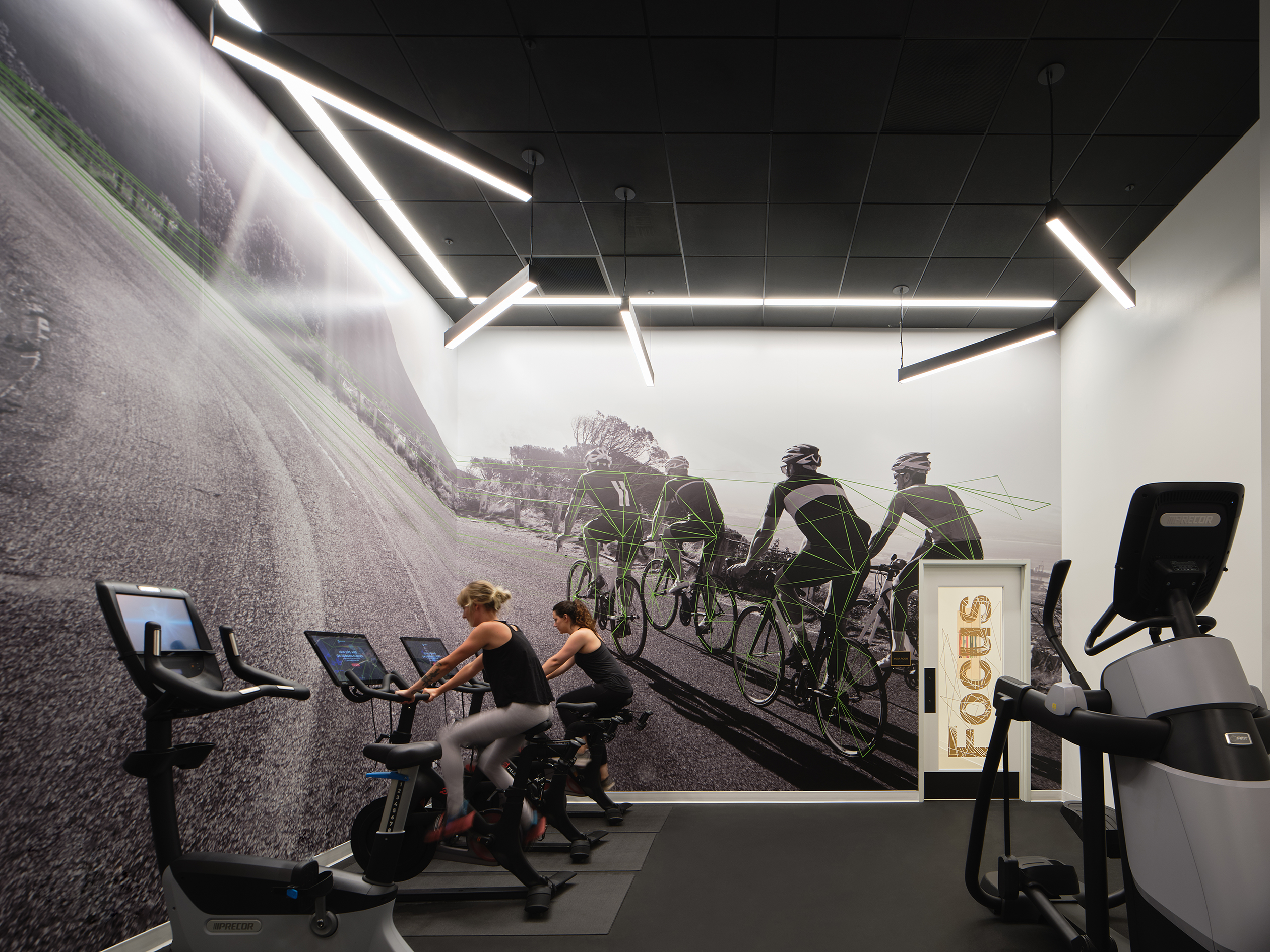 Fitness room with bikes, floor to celing graphics and two women on fitness equipment.