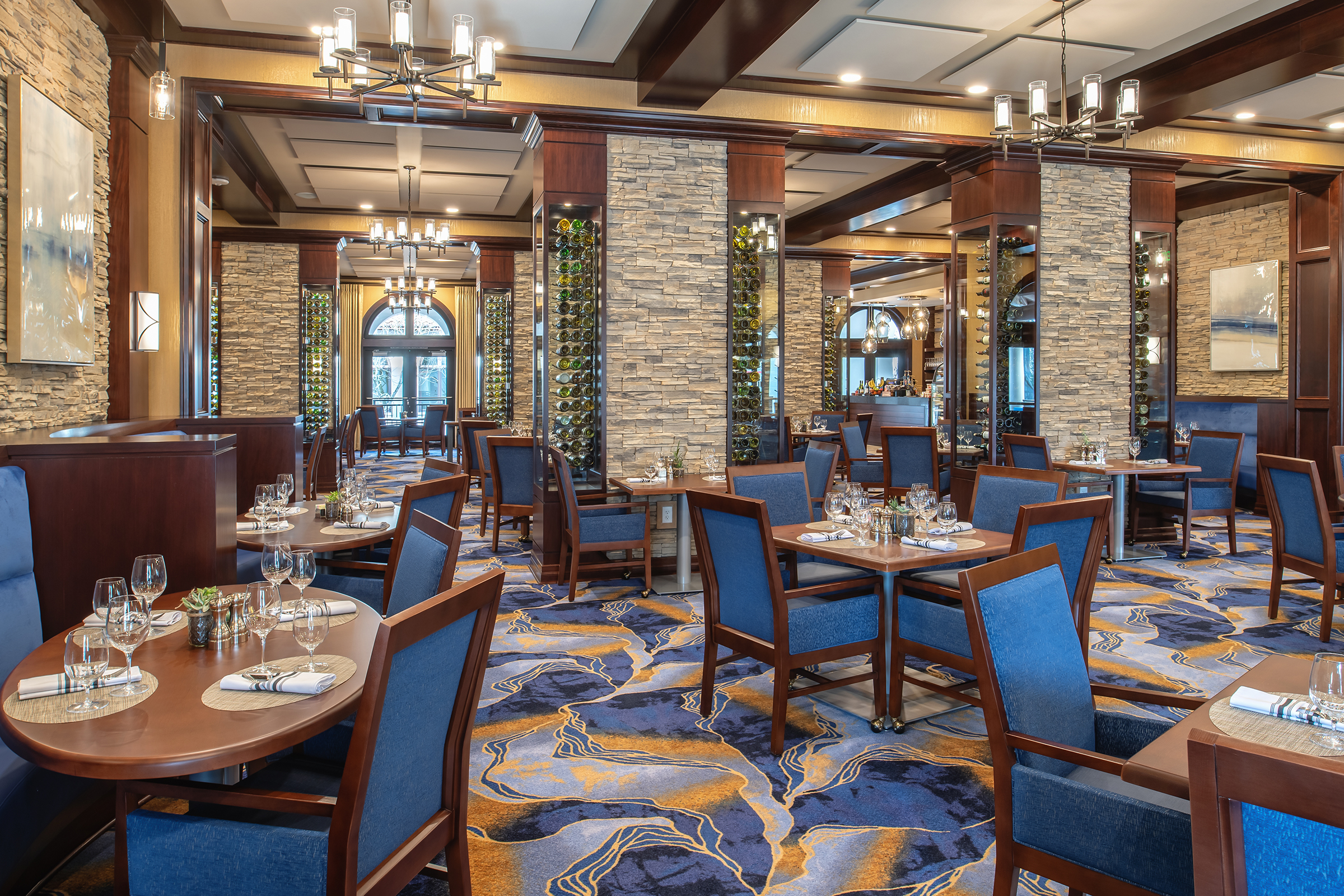 seating area of restaurant with colorful accents on chairs, stone, carpeting and wine bottle art decorations